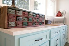 A blue kitchen in the country in Nashville, TN. Antique seed drawers with a See Rock City Birdhouse. Art by MIKA at MDV3 Gallery in Provincetown, MA. Flooring Crossville Speakeasy Zoot Suit AV282 in 12x36 from Louisville Tile. Lowes Kenroy Home Casey 7-in W Chrome Hardwired Standard Mini Pendant Lights.