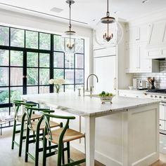 Crisp white kitchen with wall of windows. Pendants over island.