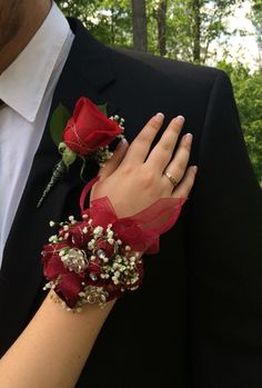Wrist corsage designed with burgundy roses, crystals, babies breath and sheer ribbon thruout, and a boutonnière rose to match.