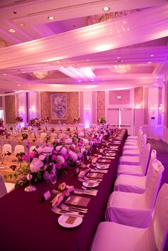 The head table, when dressed with rich eggplant floor length linen and chair covers, looks decadent with its full hedge of flowers.  Photo by Sieber Studio.