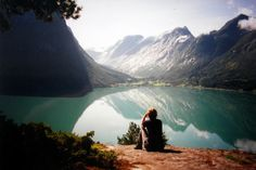 """What an awe-inspiring view. Just think of the campsite that a person could have if it were located a few feet behind the sitting person. If I were the outdoor enthusiast in this photo, I don't think I would ever want to return to the """"rat race"""" in the city."""