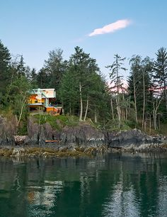 Perched high above a protected cove on its namesake isle in British Columbia, Gambier Island House—a rectilinear weekend retreat of wood, glass, and steel—was designed by theMcFarlane Green Biggar Architects + Designers for a young Vancouver-based couple. The house is nestled in its sylvan setting and features glazed walls and sliding doors, framing views of the surrounding forest.