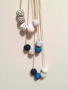 An Indigo DIY Materials colored clay suede cord or hemp a baking sheet a toothpick acrylic paint paintbrushes Directions Roll the clay into. Polymer Clay Necklace, Polymer Clay Beads, Clay Earrings, Ceramic Jewelry, Ceramic Beads, Wooden Beads, Polymer Clay Projects, Diy Clay, Bijou Brigitte