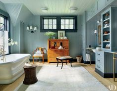 A Swedish Empire secretary and chair stand in the master bath of an upstate New York retreat by architecture firm Shope Reno Wharton and designer Thom Filicia; the beadboard walls are painted in a Benjamin Moore gray (as are the Feiss ceiling fixtures), the sconces are from Circa Lighting, the tub is by Waterworks, and the Oly bench is upholstered in goat hide.