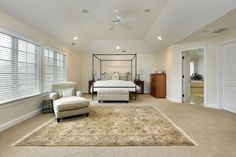 Large but sparsely furnished bedroom with off-white walls and beige carpeting.