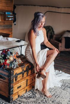 Boho bride with lace dress and purple and orange flower bouquet sitting on vintage chest and boho rug in this candid photo in Logan Utah by Kristi Alyse Photography. meaningful photography northern utah wedding and family photographer quality photography white lace dress purple orange bridal bouquet boho wedding bohemian inspo purple hair #northernutahweddingphotographer #loganutahweddingphotographer #meaningfulphotography #bohowedding #laceweddingdress #utahweddings #cachevalleyphotographer…