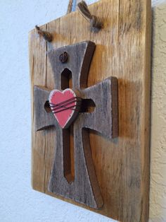 """Sign made from a recycled pallet, with a wooden cross and heart. The heart has brown wire wrapped around it. The sign hangs by jute twine.   Dimensions: 6.5"""" tall x 5"""" wide x 1.25"""" thick  Since this item was created from pallets, the wood is imperfect and will have blemishes that provide character. The pallets were cared for and given new purpose. In order to help people find purpose and hope 10% of our sales will be donated to To Write Love on Her Arms. This organization helps those with…"""