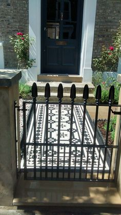 wrought iron metal gate with spear top and old style rendered wall and victorian mosaic tile path islington london