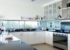 Los muebles son de melamina con herrajes de acero inoxidable, y la mesada, de granito negro absoluto. Artefacto de cocina de seis hornallas y campana Ariston.