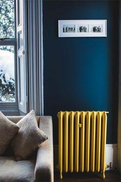 radiateur couleur jaune moutarde sur un fond du bleu canard, joli contraste des couleurs