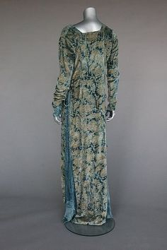 A fine and rare Mariano Fortuny stencilled velvet gown, early 20th century, `labelled Mariano Fortuny, Venise', the soft blue velvet ground stencilled in gold with Medieval style patterns, the sides inset with pleated silk and laced with silk cords and fastened with Murano glass beads