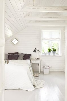 Minimalist bedroom with white walls and white floors.