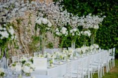 A long table ornated by high centerpieces with a mix of cherry blossom and hydrangea. Wedding by Monte-Carlo Weddings.