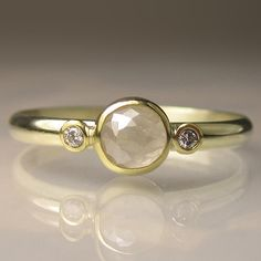 Love the finish of the stone, small diamonds on side (I normally don't like those) and small gold band .  (Rose Cut White Diamond Engagement Ring - 18k and 14k Yellow Gold on Etsy, $520.00)