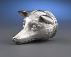 """A delightful English silver stirrup cup in the form of an upturned fox head. Expressive and intricate, the George V-era cup features an engraved crest on the underside of the jaw. Traditionally, stirrup cups were used for farewell drinks, often offered to a rider already mounted for departure. Excellent condition.<br><br>Hallmarked London, 1912<br><br>5"""" high"""