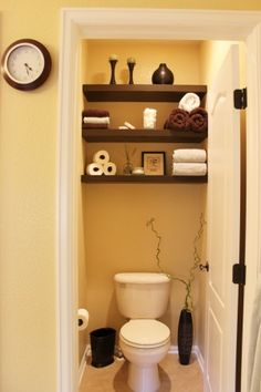 Wall to wall shelves in a tiny toilet room. Perfect for our half bath