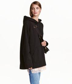 Svart. En oversized tröja i sweatshirtkvalitet med fodrad huva. Tröjan har vid passform och nedhasad axel samt känguruficka fram. Lång, vid ärm med mudd vid