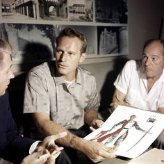 EL CID - Charlton Heston & director Anthony Mann discuss costume design with a crew member.