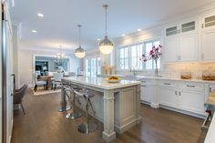 This transitional kitchen was designed by Simon Johnson. The island features maple cabinets with a Low Pur White finish in door # 200/K. Dealer: Northeast Cabinet Design