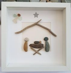 A beautiful and unique handmade beach pebble art picture nativity. Pebble parents standing looking at their new baby sleeping in driftwood cot / crib, with sea glass guardian angel. This picture is a lovely home decoration and would make a perfect gift. The picture is made using pebbles, card sea glass and driftwood. All materials are carefully placed and fixed with high strength glue onto high quality ivory hammered card. I can include printed quotes or personalised messages onto picture…