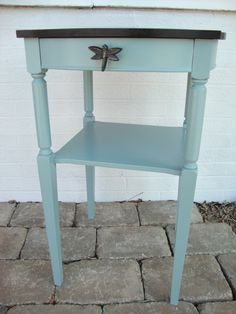 This cute side table has a stained top with a painted teal blue base. The dragonfly knob adds a whimsical touch.