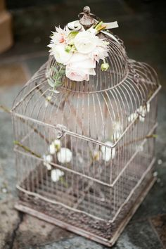 Black bird cage, white twigs/branches, teal bird, flowers tied with ribbon to the top.