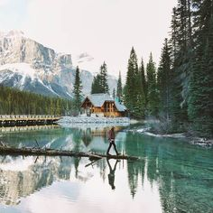 The Canadian Rockies and beautiful wood-framed Emerald Lake Lodge in the background, lush green trees on the right, turqoise waters of Emerald Lake below and a man crossing a log in the lake wearing a flannel shirt, vest and hat in the foreground.