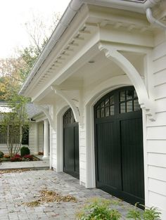 black garage doors with panes, white house and pergola