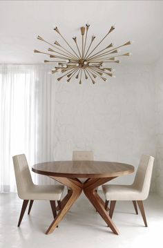 Mid-Centrury Modern interior w/ wood dining table, atomic era chandelier, upholstered chairs