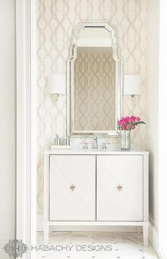 Chic art deco powder room features an accent wall clad in cream and grey trellis wallpaper lined with an art deco mirror illuminated by polished nickel sconces with half moon shades over a white footed washstand fitted with x cabinet doors adorned with star knobs atop a marble floor.