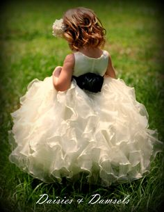 Little girls ivory organza ruffled flower girl dress, with black sash. $247.24, via Etsy.