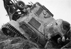"""The picture of the defeat of the French army during the German Blitzkrieg in World war 2. Soldier of Wehrmacht looks at the hearts drawn on the armor of the destroyed French tank """"Renault"""" R-35. Rear tank has a device for overcoming anti-tank ditches, trenches and – this is the heritage of the First world war.  Photo: 1940"""