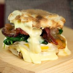 Looks like the best egg sandwich in the world. Bacon, spinach, Brie cheese on an English muffin.