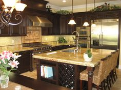 I love cooking this gormet kitchen. It has an amazing stove and frig. I love the dark wood. A huge island is a must as well.