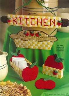 Plastic Canvas - Fill your kitchen with fresh baked sweetness! All designs are made using plastic and worsted-weight yarn. Size: Kitchen Sign: 1 x Napkin Holder: 3 x x 4 Coasters Holder: 1 x 4 x and Coasters: x 4 Skill Level: Easy - Plastic Canvas Coasters, Plastic Canvas Ornaments, Plastic Canvas Christmas, Plastic Canvas Crafts, Plastic Canvas Patterns, Kitchen Canvas, Apple Decorations, Crochet Flower Tutorial, Sewing Art