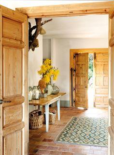 Recibidor rústico con consola con jarrón de mimosa, puertas de madera antiguas, pavimento de barro y alfombra 00383385