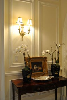 beautiful setting featuring classic wall panels and cast brass sconce with Greek urn design; wall decor ideas; wall molding; wall lighting