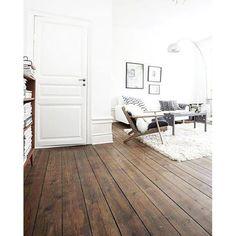 Piso de madeira escura contrastando com o branco onipresente no resto do ambiente. (E esses pisos com vincos são um charme só, não? )