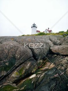 close-up view of rocks with lighthouse in background. - Close-up view of rocks with lighthouse and sky in background.