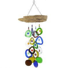 Reclaimed wine bottles of green, gold, brown and blue, sliced and melted to circular glass drops Accented with large multicolored glass beads and one-of-a-kind natural driftwood top Hardy, resilient woven filmanet line suspends the glass…