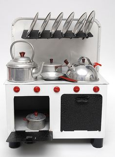"""Children's Cooking Stove ca. 1953, metal, complete with pans, plates and two kettles. Width: 6.7"""""""