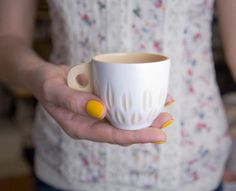 Coffee cup made of Porcelain created using colour-slip technique, covered with transparent glaze. The cup covered with transparent glaze and burned