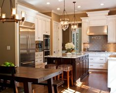 medium sized kitchen, white cabinets, dark color kitchen island, subway tile, kitchen hardwood floor