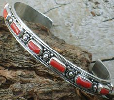 "Tibetan Coral Cuff Bracelet - sz 7.5 # TBTCI1 A wonderfully ornate red coral cuff bracelet adorned with twisted silver wire and silver drop beads, all fitting nicely on a narrow band. Bracelet has 11 individually set coral pieces with a typical dimension of 5/16"" x 1/8"". Perfect to wear as a standalone piece or as an enhancement to other bracelets or bangles.Stamped 925. $155.00."