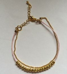 Pink string and gold beads with gold chain bracelet. Pulseira de fio rosa com bolinhas douradas e corrente dourada.