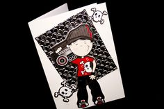 The base for this handmade children's birthday card is of a high gloss cardstock. On this is an embossed metallic silver panel. Above this is a raised cut out of a boy with his ghetto blaster on his shoulder. It is a most modern card the skull & crossbones in the corners and on the boy's shirt are a very popular trend at the moment.