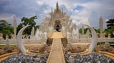 Beautiful ornate white temple located in Chiang Rai northern Thailand. Wat Rong Khun (White Temple), is a contemporary unconventional Buddhist temple.Buddhist and Hindu motifs. © YURY TARANIK / ShutterStock
