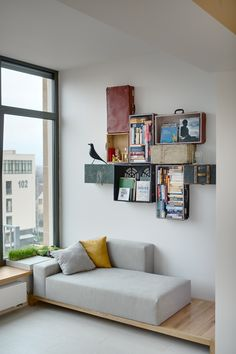 Reading corner with grey sofa on a podest and old suitcases as shelfes by Slava Balbek
