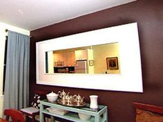 The large white mirror frames adds depth and light to a once-dark room.