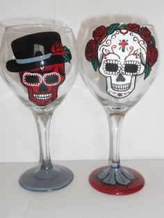 features TWO day of the dead sugar skull wine glasses.one guy and one girl...each had one single red rhinestone on it with tons of hand painted